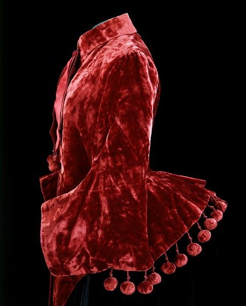 """Red velvet mantle, ca. 1885.  Dolmans were cut to lay over the back of the skirt to show off the new bustle fashion of the mid 1880s. This garment was worn by Minnie Fisher (1870-1963), the grandmother of the donor, who was born at the Old Rectory, Bathhampton, Bath.  Minnie studied at Gloucester School of Art where she won a """"South Kensington prize"""" for still-life painting."""