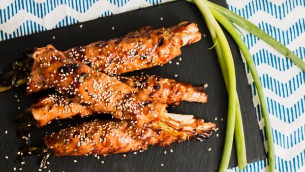 "Recipe with video instructions: Is this what they mean by, ""winner winner chicken dinner?"" Spruce up your usual chicken dinner with this Japanese negimaki-inspired dish. Ingredients: 1 1/2 pounds skinless boneless chicken breasts, 2 bunches scallions, roots trimmed and left whole, 1/4 cup soy sauce, 1 tablespoon sesame oil, 1 1/2 tablespoon apple cider vinegar, 3 tablespoons sugar, 2 garlic cloves, minced, 2 teaspoons cornstarch, 3 tablespoons cold water, Sesame seeds..."