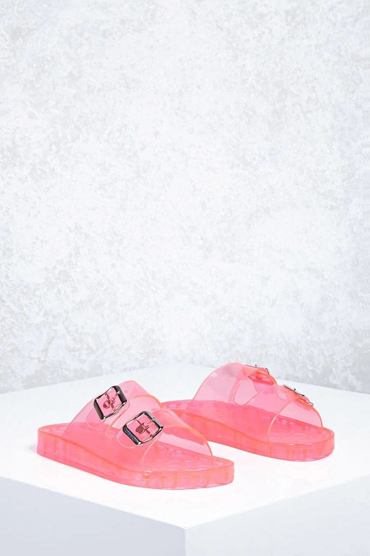 A pair of clear jelly sandals featuring a dual strap design with buckle accents, and a slip-on style.