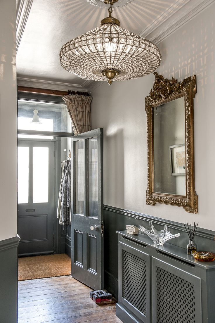 The hallway has been painted a deep shade of grey with accents of gold and sparkling glass provided by the beautifully shaped chandelier, another find from Hastings Antiques Centre