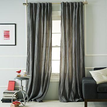 Elemento decorativo. Cortinas correderas en colores grises. Rompen con el color blanco de las paredes de la habitación.