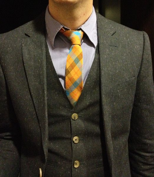 Bright skinny tie with a dark gray suit. A tie clip would be cool too. <3