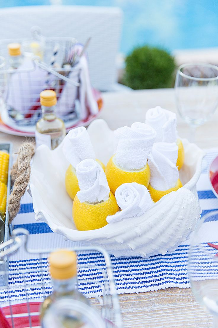 Rolled towels tucked in lemons, perfect for those messy meals!  Lobster boil beach wedding or rehearsal dinner.
