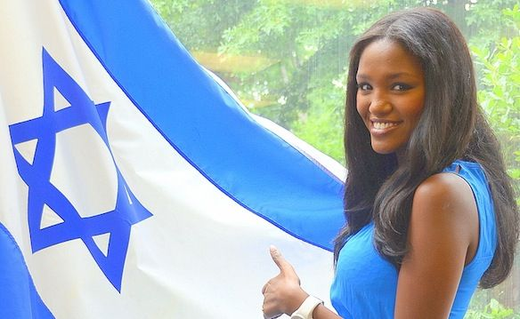 """Yitayish Ayenew, the first black Miss Israel and also the first woman of Ethiopian heritage to win the crown, poses with the Israeli flag at Solomon Schechter Day School of Bergen County, NJ, on June 14.  """"Part of being Jewish is being in the state of Israel,"""" she told the Solomon Schechter students, with visible emotion. """"To be a Jew is to keep the tradition, to continue to be who we are. I am proud to be a Jew.""""  Photo by Maxine Dovere."""