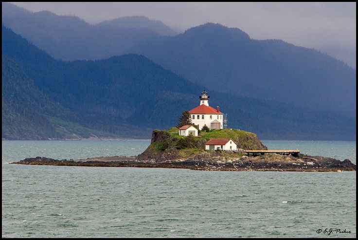 The Magnificent Eldred Rock Lighthouse Surrounded By Many Mountain Ranges