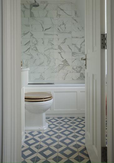 Bathroom - panelled tub skirt, large marble subway tiles, patterned floor tile