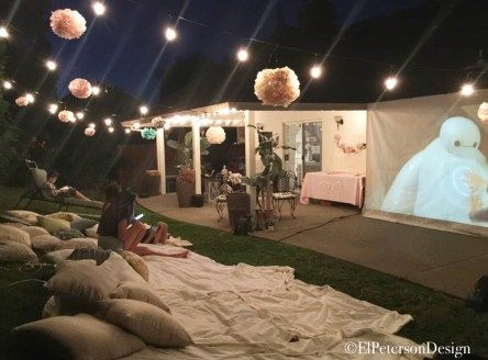 tarp movie screen and outdoor lights; duvets, blankets and pillows; popcorn and drinks station outside with balloons