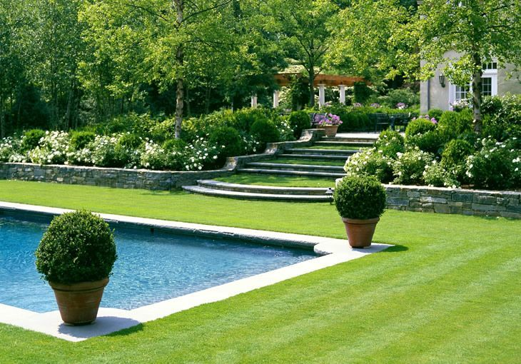 Terraced grass steps sloping down the hill pool