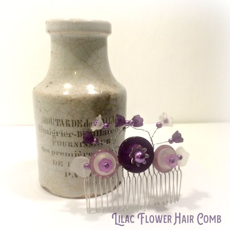 Lilac flower hair comb embellished with buttons, pearl effect beads and lucite leaves with wire sprigs topped with lucite flowers.