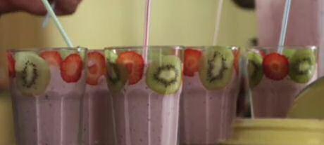 Basis recept om smoothies te maken met bevroren kleinfruit, roomijs, yoghurt en melk, glazen versierd met dunne schijfjes fruit