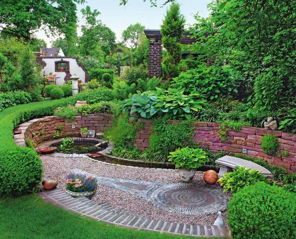 Садовый уголок у основания склона оформлен с большой фантазией. Изюминка места отдыха — мозаика из гравия посреди засыпанной щебнем площадки. Узор дублирует форму водоема.