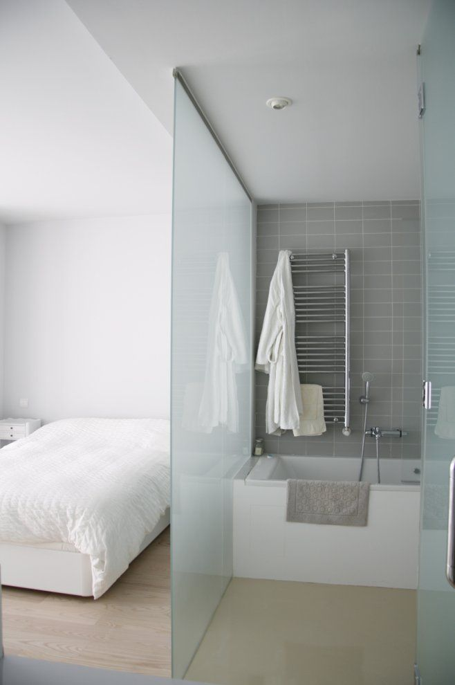 The idea of a frosted or translucent glass divider or full glass wall  between bedroom & bathroom .