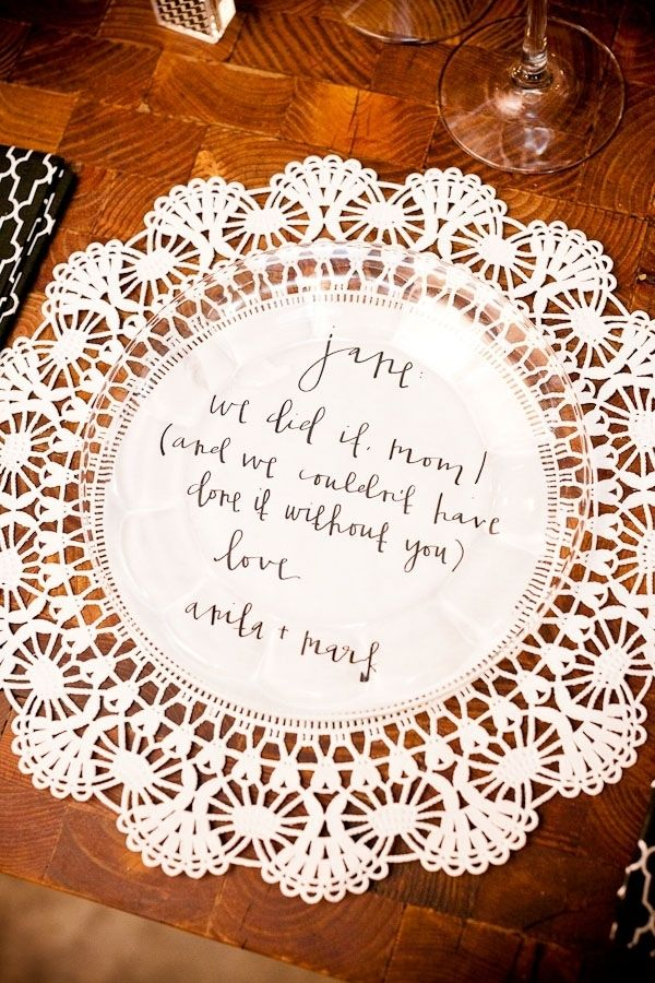 rather than use tableclothes or placemats, this couple bought large, white doilies and came up with personal messages for their guests that the bride hand-wrote in her amazing and unique calligraphy