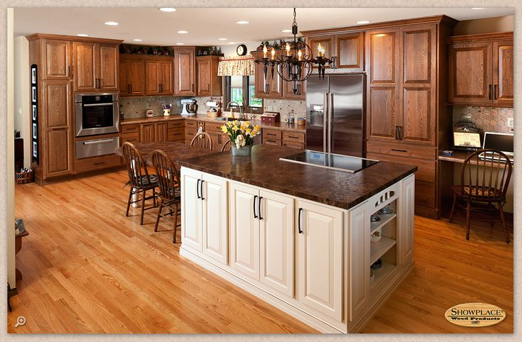 A wall was removed to open the kitchen into the spacious setting shown here. Traditional comfort was the goal, and Showplace red oak provides it in the warm Cognac stain. A bright counterpoint is introduced with the painted island.