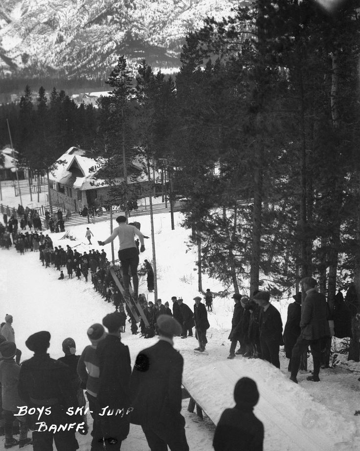 #RockiesThrowback: Banff Winter Carnival boys ski jump Wolverine Street.  We recommend you wander up there (to the base of the Ken Madsen Trail in Banff Alberta) and see for yourself if the clear-cut is still visible today.   Created by Byron Harmon 1920. Courtesy of The Whyte Museum of the Canadian Rockies V263 / NA - 3980  #MountainCultureElevated | Banff Centre for Arts and Creativity | #whytemuseum