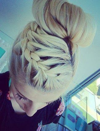 For a fun spin on your bun, try doing a side part and French braiding your hair into the bun. This style is sure to keep frizz and flyaways at bay.