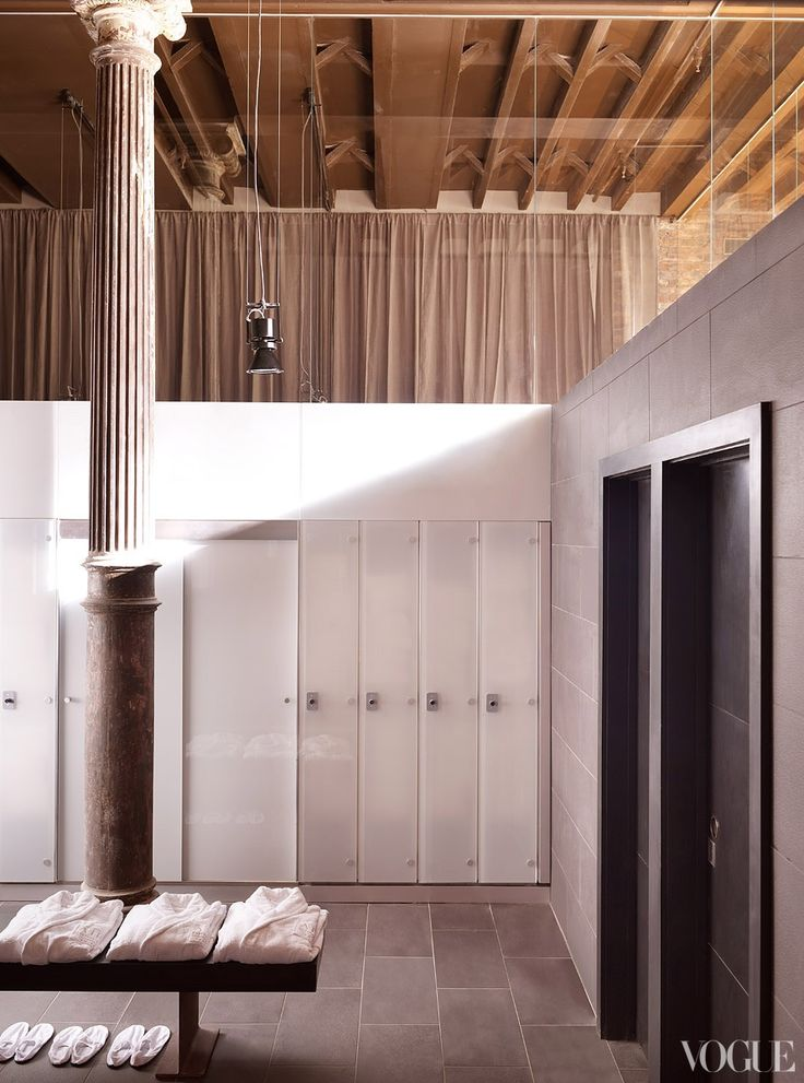 exposed ceiling, slate floors, white lockers with black benches and vanity