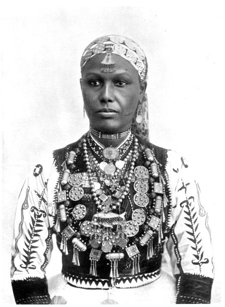 Africa | An Abyssinian Woman - Over a richly-embroidered silk shirt, an Abyssinian woman wears elaborate jewellery of beautiful design and workmanship. She wears bracelets, ear-rings, bangles on her wrists and ankles, and is very fond of perfumes' | Image and caption from 'Customs of the World', printed in 1900; photograph by Lekgian & Co.