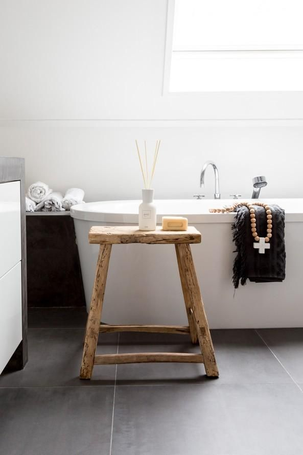 Keep a rustic stool by the side of a modern bath and add a glass of wine
