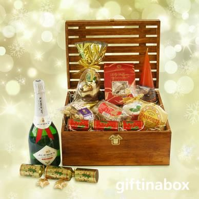 Filled to the brim with first class gourmet delights and fine sparkling wine, this beautiful festive season wooden crate with a hinged lid will be sure to make an impression, even on Santa Claus.  Christmas pudding Milk chocolate snowy the snowman 160g Sally Williams almond gift box Paneforte margherita Mini Christmas cake Mixed nuts 2 x Christmas crackers Bottle of JC Le Roux sparkling wine 2 x chocolate Christmas lollipops 2 x chocolate festive mini slabs
