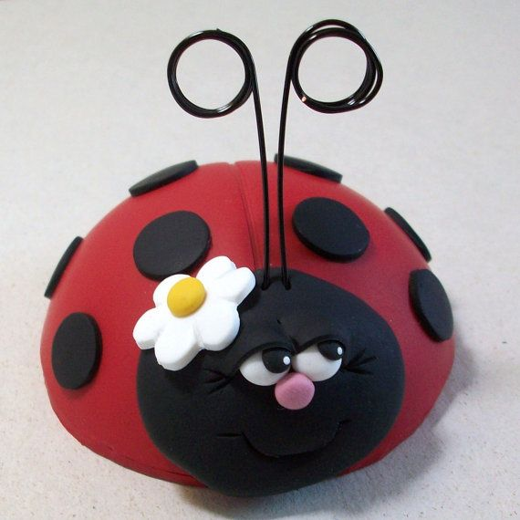 Adorable Ladybug cake topper or center piece with a little white flower secured to her head. Her antennae will hold notes or photos. Ladybug cake topper