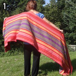 Rebozo, krok 1: Šatku si prehoďte cez chrbát - jedna časť smeruje popod pažu, druhá ponad rameno.