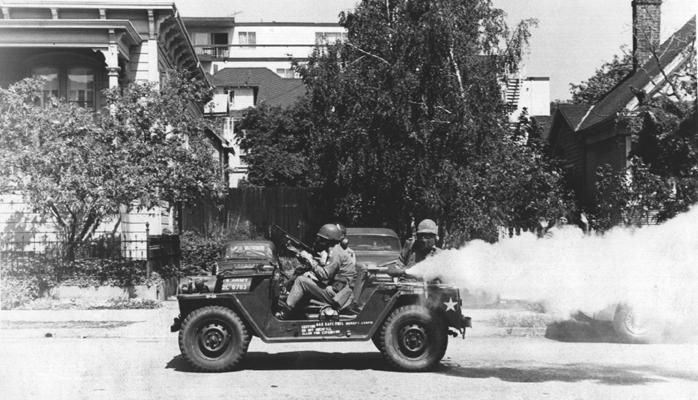 "Alameda County Sheriffs drive a jeep outfitted with a pepper fogger through a Berkeley neighborhood during the ""Bloody Thursday"" suppression of protests at People's Park (1969)"