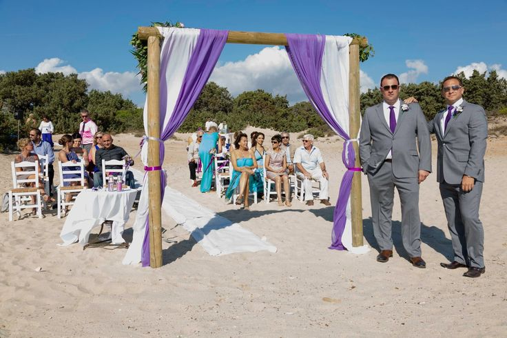 Ready for the bride - white wooden taverna chairs awaiting their guests on Alyko beach Naxos Greece - wooden wedding arch with purple gauze and flowers by Anemona flower shop Naxos Greece #destinationwedding #greecewedding