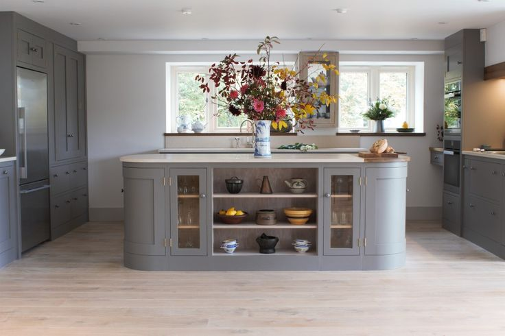 Sustainable Kitchens - A beautiful open plan barn conversion with a shaker kitchen painted with Farrow & Ball moles breath. Open shelving with glazed cabinets on a curved centre island topped with marble worktops.