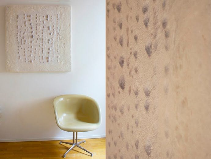 Apeìron Wall Lamp in felt - Judith Byberg Architetto & Designer. Apeìron Wall Lamp in felt Material: carded Bergschaf wool, silk Chiffon natural white and seeds from fruit. Structure in wood 96 x 95 x 5 cm. Led light.
