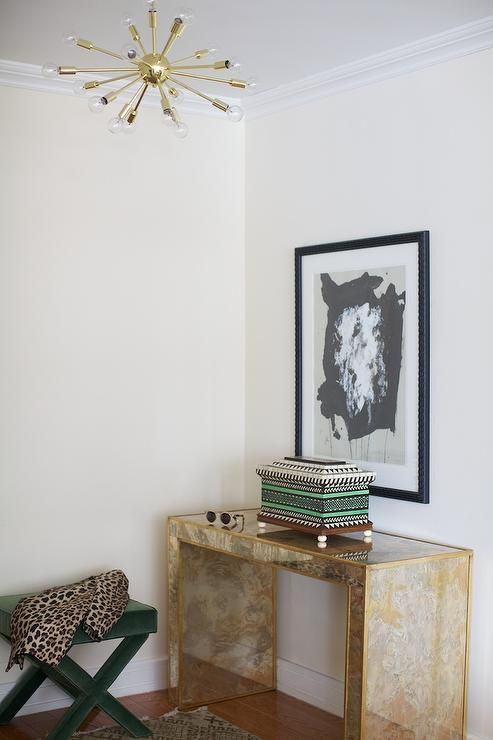 Chic foyer features a gold mirrored waterfall console table, Worlds Away Madison G Console Table, under art illuminated by a brass sputnik chandelier alongside an emerald green velvet x bench draped in a leopard print scarf.