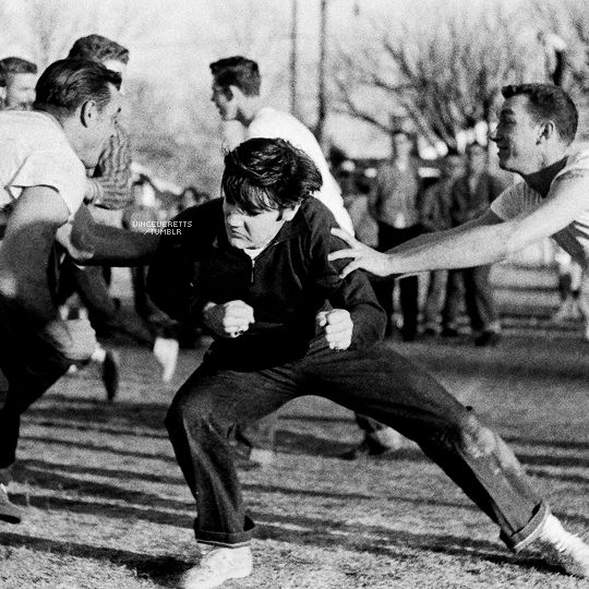 """Elvis Presley playing touch football at the Dave Wells Community Center December 27, 1956. Several hundred people watched the singer pass, kick and run a touchdown. Elvis's first movie, ""Love Me..."