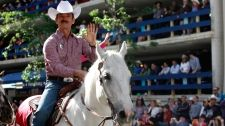 Calgary Stampede parade marshal and astronaut Chris Hadfield waves to the crowds during the Calgary Stampede parade in Calgary, Friday, July 5, 2013. (Jeff McIntosh / THE CANADIAN PRESS)