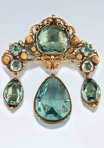 An early 19th century paste brooch  Of girandole design set with 'aquamarine' coloured vari-shaped mixed-cut pastes, the shaped surmount with central cushion-cut single stone and square and circular accents within a cannetille surround, suspending triple pear shaped drops, in gilt metal mounts with coloured foil backs, circa 1830, the central drop in open mount