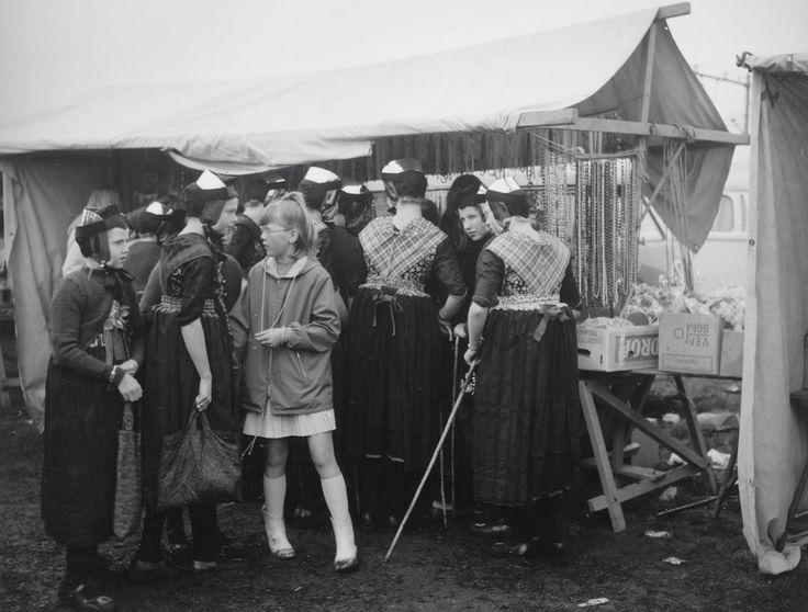 Meisjes in Staphorster streekdracht bij een kraam op de jaarmarkt te Staphorst. De jaarmarkt vindt plaats op de derde dinsdag van april. De meisjes dragen opknapdracht met het 'blote' oorijzer. 1969 #Overijssel #Staphorst