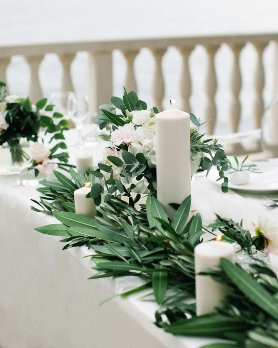 Olive branches and arrangements of roses, blush oleander, hydrangeas, and eucalyptus from Martin Heard Designs surrounded ivory pillar candles in various sizes at this Croatian wedding.