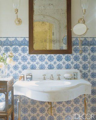 In a Montecito, California, guest bath designed by Michael S. Smith, tiles reproduced from antique Portuguese originals and an antiqued mirror make the new Portuguese-style manor home feel old—in a good way; the sconces are by Vaughan.