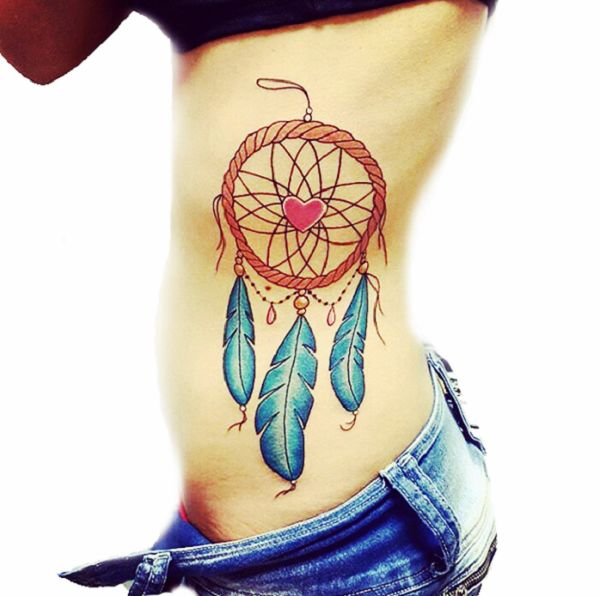 Rib Dreamcatcher Tattoo Design with Cute Heart. The heart within the dreamcatcher depicts the harmony in love. You can embellish your rib with this amazing tattoo and can surprise your loved one.