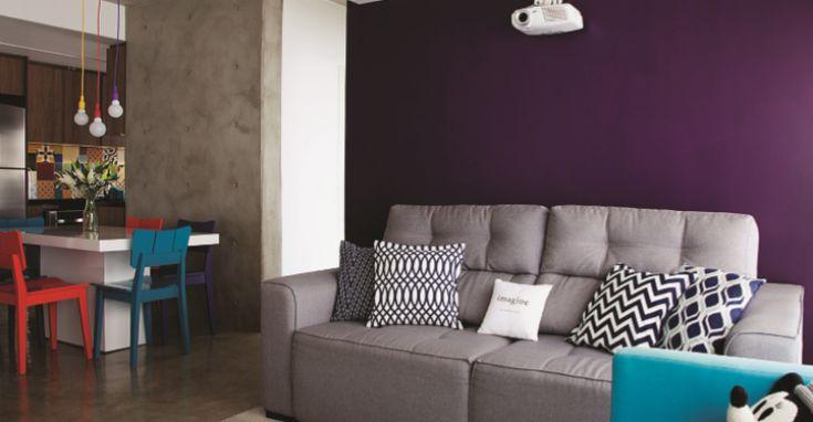 Sala de estar / home theater / projetor / cimento queimado / parede roxa / sofá cinza / poltrona azul / mesa branca / cadeiras coloridas / luminárias coloridas