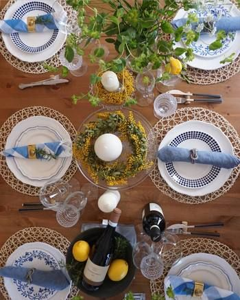 かご素材のマットをひいて、テーブルの木目をあえて見せるナチュラルなセッティング。すべて柄の違うお皿・ナプキンホルダーの使い方は真似したいコーディネートテクニックですね。ミモザやレモンのイエロー、テーブルナプキンやお皿のブルーが爽やかな差し色に。