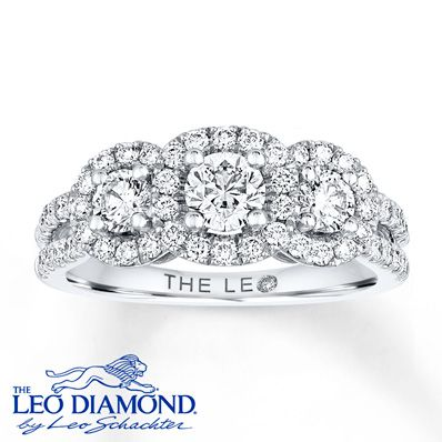 This three-stone Leo Diamond engagement ring features a trio of round diamonds, with more round diamonds framing each. Additional round diamonds line the 14K white gold split-shank band, bringing the total diamond weight to 1 1/5 carats. The center diamond is laser-inscribed with a unique Gemscribe® serial number. Diamond Total Carat Weight may range from 1.18 - 1.22 carats.