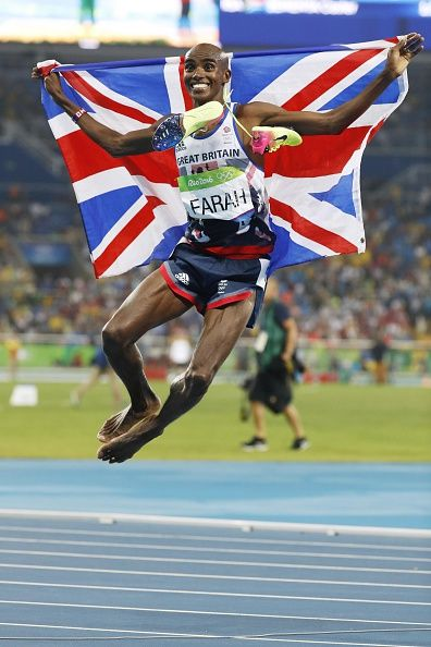 Mo Farah of Britain jumps in the air with the country's national flag as he…