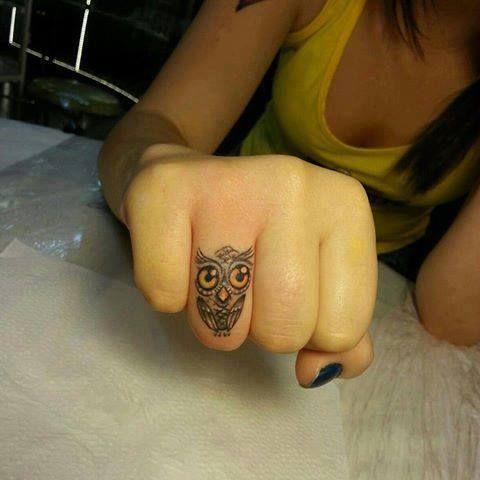 Pequeño tatuaje de un búho en el dedo.