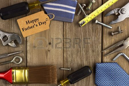 Happy Fathers Day gift tag with frame of tools and ties on a rustic wood background photo