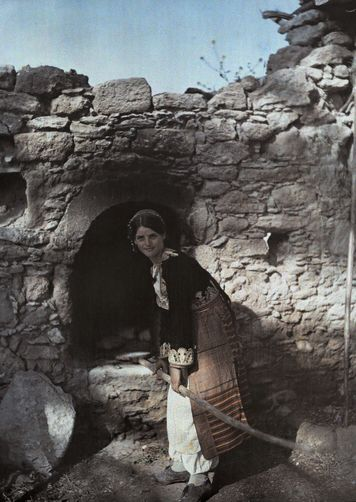 A girl holds a paddle in an outdoor oven. Rizokarpasso-Cyprus. National Geographic's Greece in Color from the 1920s Photographer: Maynard Owen Williams in the 1920s