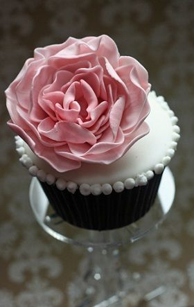 amazingly frosted white wedding cupcake with a beautiful pink rose