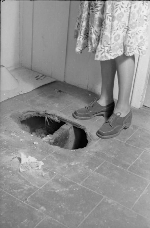A DAY IN THE LIFE OF A WARTIME HOUSEWIFE: EVERYDAY LIFE IN LONDON, ENGLAND, 1941. Mrs Day stands alongside a hole in the floor which was made by a fire bomb before the fire was brought under control. This area of the house does not have asbestos sheeting on the floor.