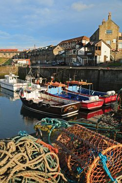 """Boats in harbor, Seahouses, England, UK  Though no longer a major industry, fishing is still very much a part of life in Northumberland. Scenes like this one in the village of Seahouses are common. I included fishing gear in this composition to complete my """"fish"""" story."""