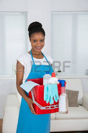 Smiling African Woman Holding Basket With Cleaning Equipment photo