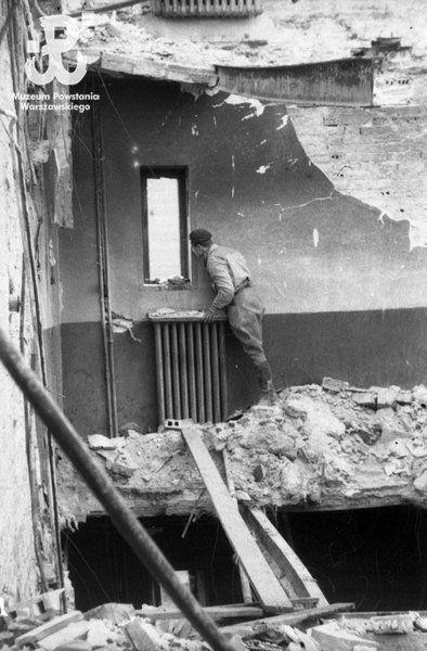 Observation post on the fourth floor of the ruined building at ul. Marszałkowska 31. At the window  is kpr. pchor. Stanisław Kubin 'Tadzio' of 3rd Company of Battalion 'Golski'.